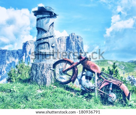 Old abandoned red motorbike on a mountain landscape. Vintage filter - stock photo