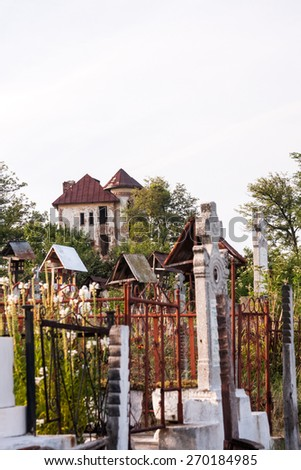 Old, abandoned, ruined house in the field with cemetery next to it - stock photo
