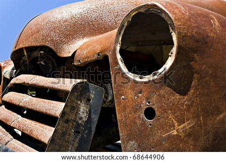 Old abandoned rusted truck - close up abstract with focus on the inside of the empty headlamp - stock photo