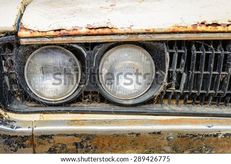 Old abandoned rusty car covered with web. Front view  - stock photo
