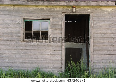 Old abandoned school building in high grass with broken windows and missing doors with rusty light - stock photo