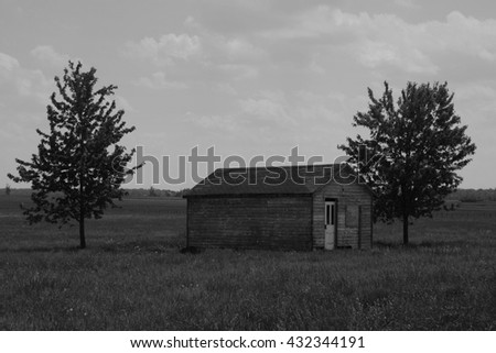 Old abandoned school in a pasture in black and white