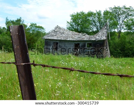 Old abandoned shed in rural field - stock photo