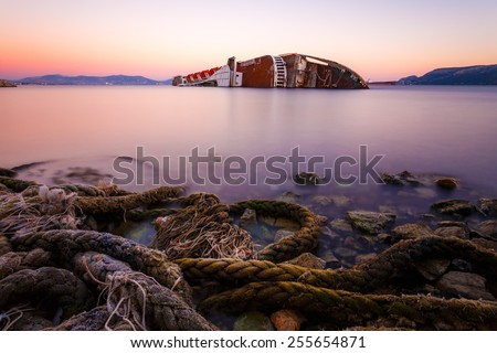 Old abandoned shipwreck near Elefsina, Greece against a colorful sky, long exposure photograph - stock photo