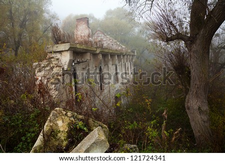 Old abandoned stone mill nineteenth century among the thickets of trees - stock photo