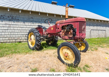 Old abandoned tractor in grass field by an abandoned barn.  - stock photo
