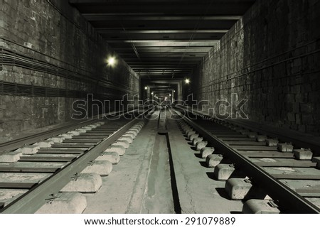 Old abandoned train rails in a tunnel - stock photo
