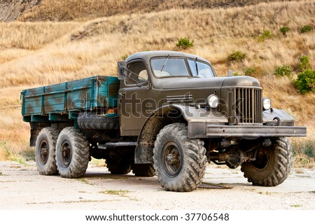 Old abandoned truck standing alone in the field - stock photo