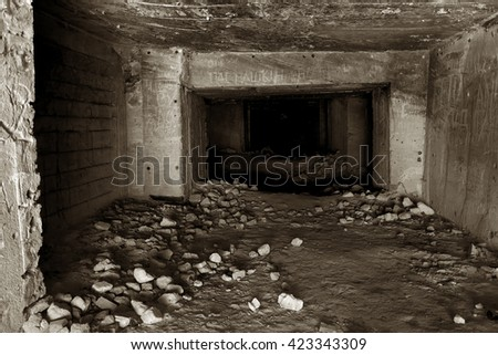 Old abandoned tunnel in underground quarries. Entrance to the catacombs. Black / white photo style effect it film grain. Selective focus. As a creative background for the design of the dark - stock photo