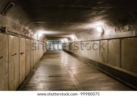 Old abandoned underground tunnel partly illuminated with lamps - stock photo