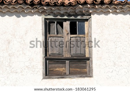 Old Abandoned Window with Broken Glass over a White Wall