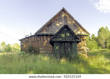 Old abandoned wooden house among wild tall weeds fisheye view. Berezichi, Kaluzhskaya region, Russia.
