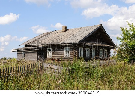 Old abandoned wooden house with slate roof in northern russian village, sunny summer day - stock photo