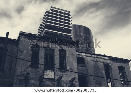 Old abandoned wrecked house and modern building at backgrounds. Tel Aviv (Israel). Time concept. Toned dark photo. - stock photo