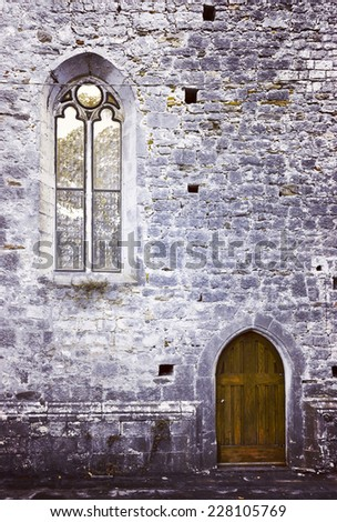 Old abbey stone wall with entrance door and tall arched window. - stock photo