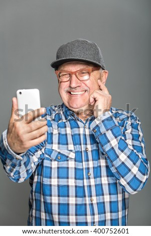 Old active man taking selfie with mobile phone isolated on grey background - stock photo
