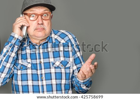 Old active man using mobile phone isolated on grey background