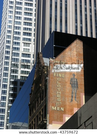 Old advertising sign with a new building background. - stock photo