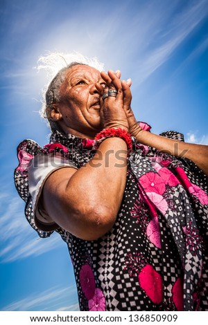 old african homeless lady in open prayer with the sky as a background - stock photo