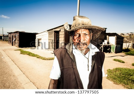 old african man in the streets of the township wearing an old farmers hat - stock photo