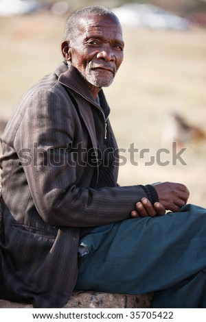 old African resting on a stone, blurred African desert background