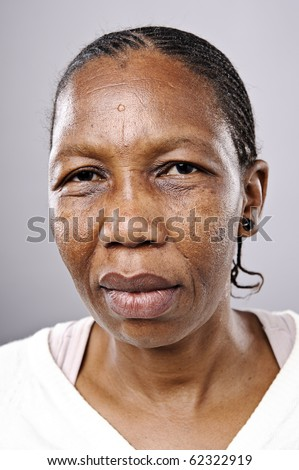 Old African woman looks at camera with sad eyes - stock photo