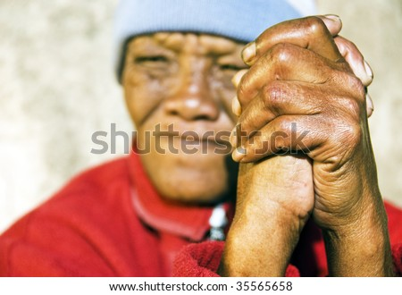 Old African woman with focus on her weathered folded hands - stock photo