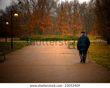 Old age concept. Man walks in autumn park - stock photo