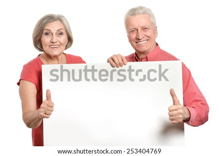 Old age couple holding blank banner ad against white background - stock photo