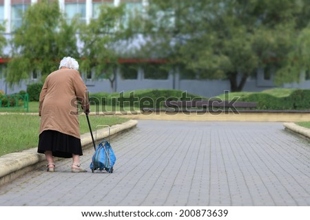 Old age - no joy. Old woman with bag seen from behind. Grandmother tired. - stock photo