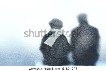 old age - old couple sitting in a bus stop - stock photo