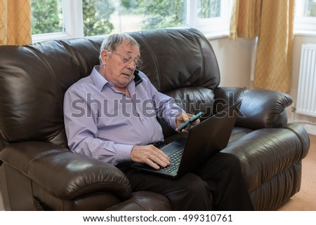 Old age Pensioner trying to use modern electronic devices like laptop and mobile phone.
