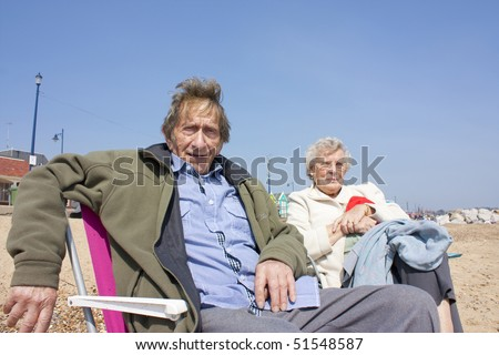 old age pensioners on the beach in spring, essex, uk - stock photo