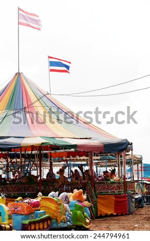 old aged colorful riding animals horses rabbits ducks toys in a large playground as circus carousel tent in a country fair in LOY KRATHONG Festival THAILAND with THAI flags in the wind above  - stock photo