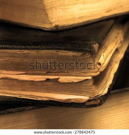 Old aged grungy vintage books sepia closeup, large detailed macro, gentle bokeh, black leather cover - stock photo