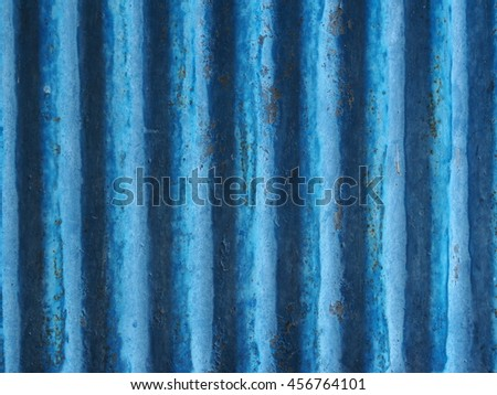 old aged weathered galvanized corrugated iron metal sheet surface painted in blue for use as backdrop background  - stock photo
