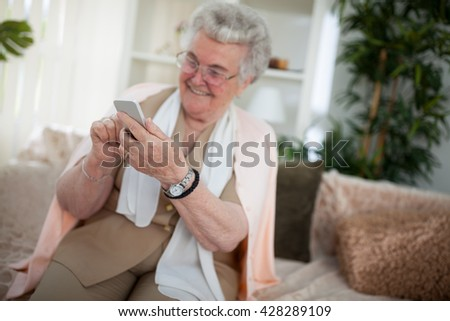 Old aged woman smiling and using a smartphone - stock photo