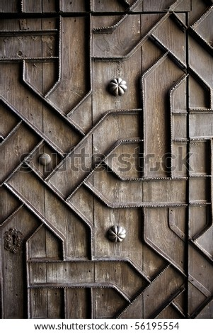 old aged wooden door with iron handcraft deco work spain church - stock photo