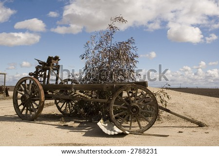 Old agricultural wagon on a farm in California with cumulus clouds in background