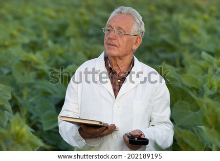 Old agronomist in white coat looking ahead in field - stock photo
