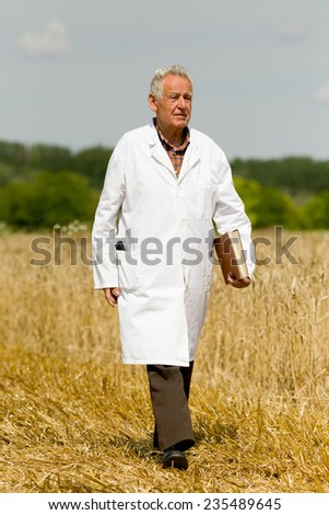 Old agronomist in white coat with notebook walking on wheat field - stock photo