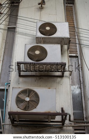 Old air conditioner compressor with rust on the wall outdoor