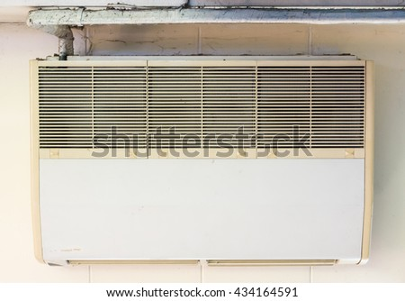 Old air conditioner unit is hanging on the office ceiling. - stock photo