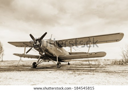 Old airplane on field in sepia tone - stock photo