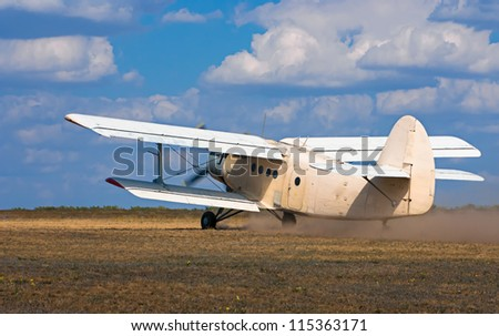 old airplane takes off on the field - stock photo