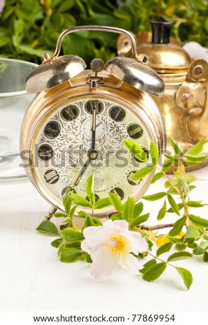 Old alarm-clock and teapot with wild flowers on white table - stock photo