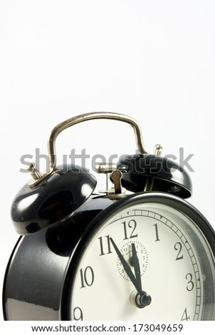 Old Alarm Clock isolated on white background, showing five to twelve  o'clock