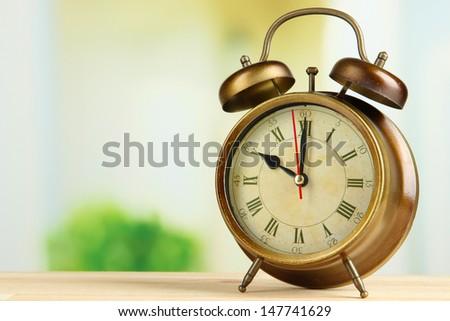 Old alarm clock  on bright background - stock photo