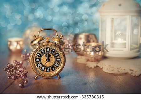 Old alarm clock set to five to midnight on decorated table with candles. Happy New Year 2016! - stock photo