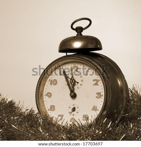 Old Alarm Clock showing few minutes to twelve sepia tone - stock photo